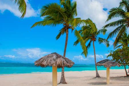 View of Playa Esmeralda in Holguin, Cuba. Caribbean sea. Beautiful Paradise beach: umbrellas, sea, palm trees sand. Tropical landscape