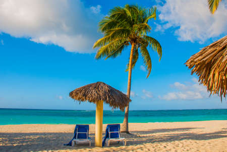 Holguin, Cuba, Playa Esmeralda. Umbrella and two lounge chairs around palm trees. Tropical beach on the Caribbean sea Banco de Imagens - 99616558