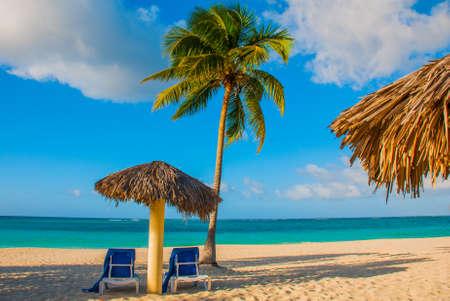 Holguin, Cuba, Playa Esmeralda. Umbrella and two lounge chairs around palm trees. Tropical beach on the Caribbean sea. Paradise landscape. Stock Photo