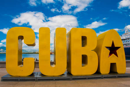 The inscription of the CUBA. Huge letters on the waterfront, against a blue sky with clouds in Santiago de Cuba