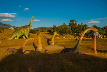 Statues of dinosaurs in the clearing. Prehistoric animal models, sculptures in the valley Of the national Park in Baconao, Santiago de Cuba, Cuba. Stock Photo