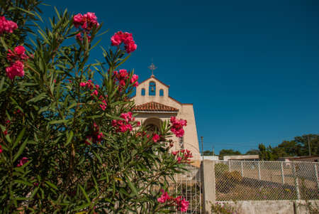 Red flowers in the background Catholic Church in a village near the town Cienfuegos in Cuba. Stock Photo