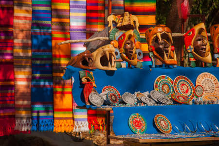 Souvenirs from Mexico in the market. Mexican Mayan crafts, embroidery on fabric, plates, pyramids. Sale for tourists with gifts. Stock Photo