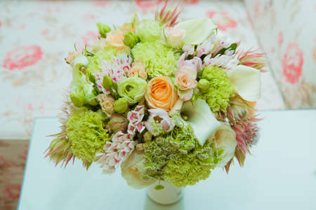 A beautiful brides bouquet of delicate shades of green, pink, orange and white flowers is in a vase on the wedding day. Фото со стока