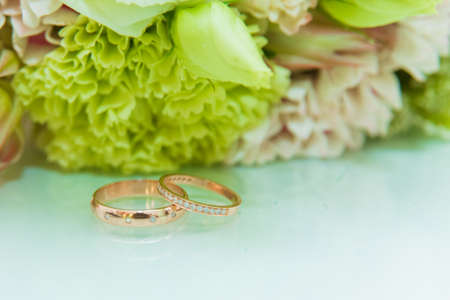 Wedding ring. Two gold rings with diamonds of the bride and groom are on a white surface.