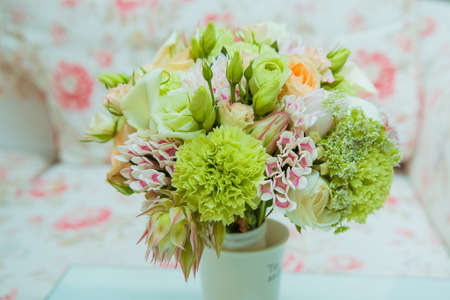 A beautiful brides bouquet of delicate shades of green, pink, orange and white flowers is in a vase on the wedding day Фото со стока