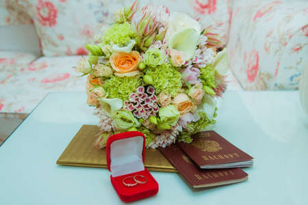 Wedding ring. Two gold diamond rings of the bride and groom are in a red box near the brides bouquet of delicate flowers and passports of the Russian Federation.