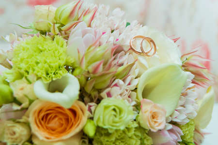 Wedding ring. Two gold rings with diamonds bride and groom and a bouquet of delicate flowers Фото со стока