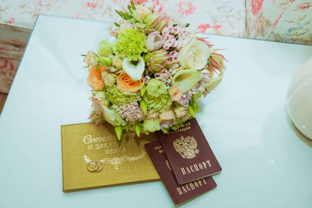 Wedding ring. Two gold rings with diamonds are in a red box, next to the brides bouquet, marriage certificate and passport of the Russian Federation. Фото со стока