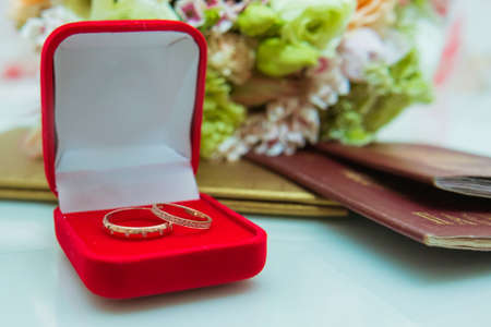 Wedding ring. Two gold diamond rings of the bride and groom are on in a red box near the brides bouquet of delicate flowers.