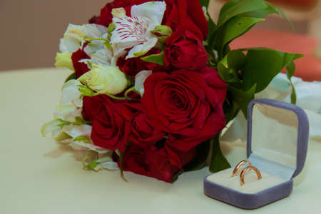 Wedding ring. Two gold vintage rings of the bride and groom with diamonds are in a blue box and a bouquet of red roses and white flowers Фото со стока
