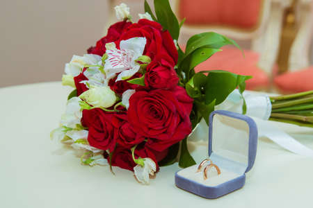 Wedding ring. Two gold vintage rings of the bride and groom with diamonds are in a blue box and a bouquet of red roses and white flowers.