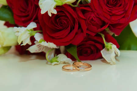 Wedding ring. Two gold vintage rings of bride and groom with diamonds and a bouquet of red roses and white flowers