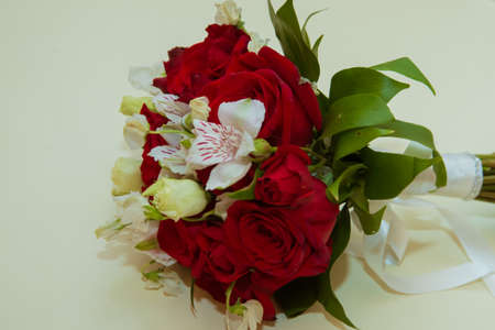 Beautiful brides bouquet of red roses and white flowers on the wedding day.