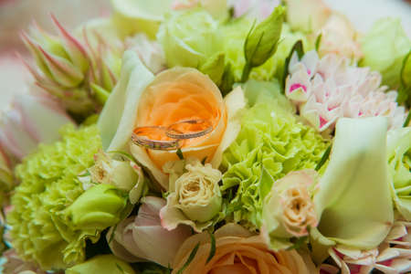 Wedding ring. Two gold rings with diamonds bride and groom and a bouquet of delicate flowers. Фото со стока