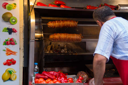 Istanbul, Turkey: A man is cooking meat on the street. Street vendor roast meat on a spit. Traditional popular dish.