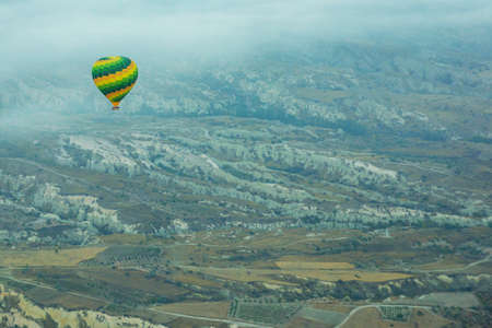 Cappadocia, Turkey: Flying in a balloon. Top view in the early morning, misty landscape with balls.The great tourist attraction of Cappadocia - balloon flight.