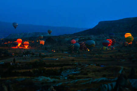 Goreme, Anatolia, Turkey. Beautiful sunrise over the valleys. In the sky flying balloons. Favorite entertainment for tourists.Traveling concept background.