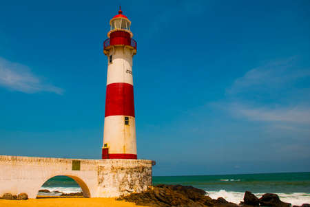 SALVADOR, BAHIA, BRAZIL:Farol De Itapua on the rough sea. Lighthouse on the beach in Sunny weather. South America