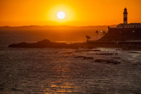 SALVADOR, BRAZIL: Portrait of the Farol da Barra Salvador Brazil lighthouse. Beautiful landscape with verm at sunset. America Banco de Imagens