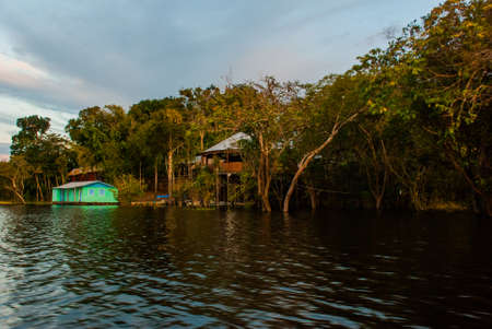 Amazon river, Manaus, Amazonas, Brazil, South America: Amazon landscape with beautiful views. Wooden houses on an island on the Amazon river in the jungle.