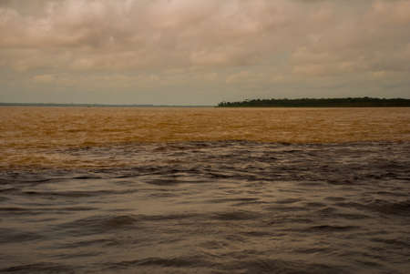 Manaus, Amazonas, Brazil, South America:The merger of the two colored river, Rio Negro, Solimoes. Meeting, multi-colored waters do not mix, and continue the way side by side, thus each river remains with the own color.