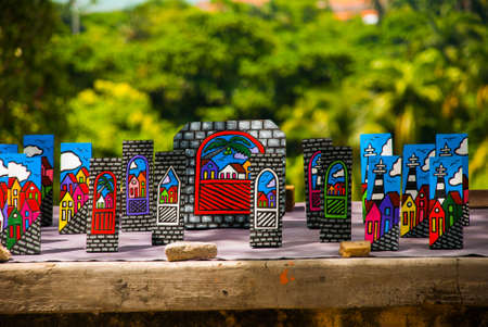 OLINDA, PERNAMBUCO, BRAZIL, Market: Brazilian art and craft carved on a tree bark and painted with vibrant colors representing the colorful building of Olinda in Pernambuco, Brazil.