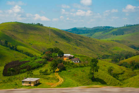 Beautiful landscape overlooking fields and hills with white clouds and blue sky. Brazil, America.