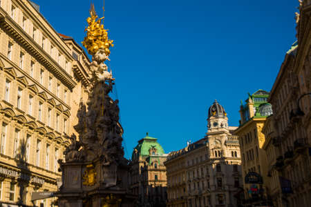 VIENNA, AUSTRIA: memorial Plague column Pestsaule and tourists on Graben street Vienna. The Graben is one of the most famous streets in Vienna first district, the city centre. Europe
