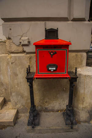 Budapest, Hungary. Bright red mailbox with a slot for letters, with a relief image of the mail horn, with legs supports