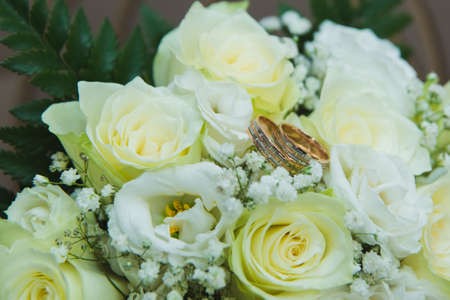 Beautiful delicate wedding bouquet of white roses and wedding rings of the bride and groom. Wedding day. Stock Photo