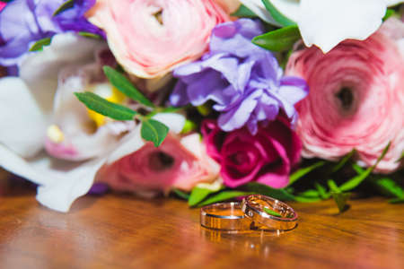 Wedding rings of the bride and groom on a Beautiful wedding bouquet. Wedding day.