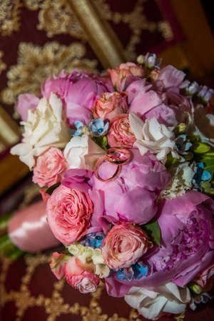 Wedding rings of the bride and groom on a Beautiful wedding bouquet of pink peonies and roses. Wedding day.