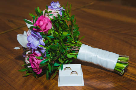 Wedding rings of the bride and groom on a Beautiful wedding bouquet. White ring box. Wedding day.