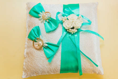 Wedding rings are on a white pillow and sadely the brides bouquet. Wedding day.