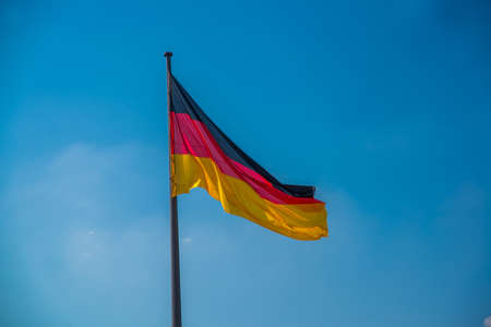Silky flag of Germany flying in the wind. Flag against the blue sky.