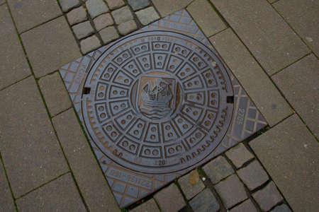 Closed manhole cover on a city street. Helsingor, Elsinore, Denmark, Europe