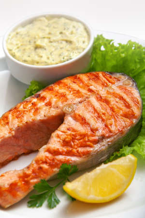 fish dish: grilled salmon steak with sauce, parsley and lemon  Stock Photo