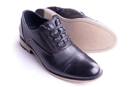 A pair of mens shoes, one on the side, isolated photo