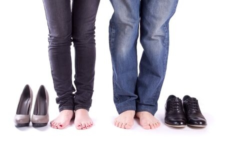 legs around: Man and a woman barefoot around their shoes isolated
