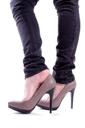 tacones negros: La mujer se quita el zapato con pies aislados