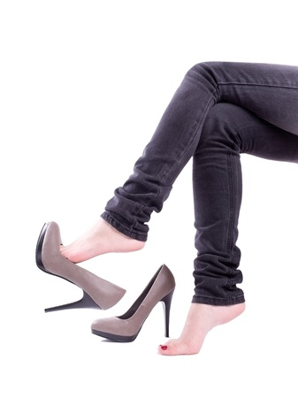 women in jeans: The woman sit and took off her shoes isolated Stock Photo