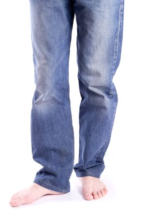 Mens feet barefoot in jeans isolated photo