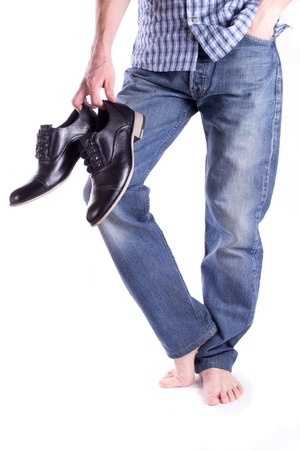 Mens feet barefoot and holding a pair shoes isolated Stock Photo