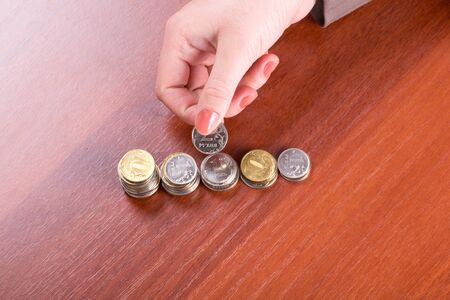 Woman's hand puts a coin in the pile Stock Photo - 12075382