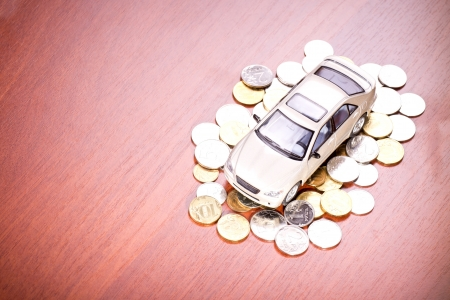 car loans: Model car on a placer of coins on the table