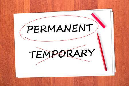strikethrough: Chose the word PERMANENT, crossed out the word TEMPORARY Stock Photo