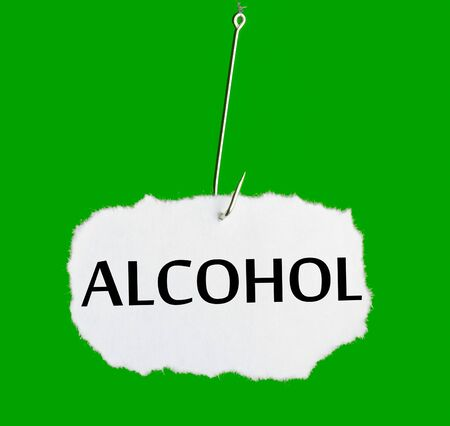 Word ALCOHOL on a fishing hook on green background photo