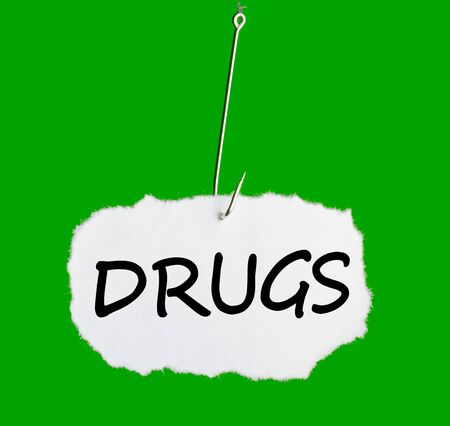 Word DRUGS on a fishing hook on green background photo