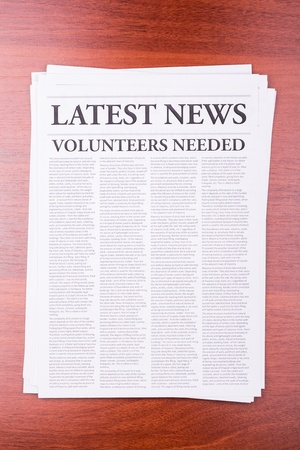 The newspaper LATEST NEWS with the headline VOLUNTEERS NEEDED Stock Photo